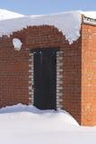 Porta chiusa bloccata del metallo coperta di neve Costruzione del muro di mattoni Fotografia Stock Libera da Diritti
