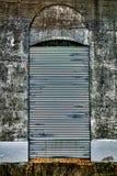 Porta d'acciaio di sicurezza della tenda sulla fabbrica abbandonata Immagini Stock Libere da Diritti