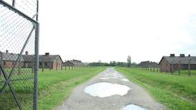 Porta da entrada e a cerca elétrica do campo de concentração com casernas filme