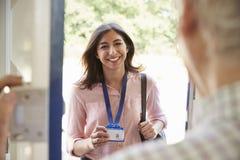 Porta da rua da abertura do homem superior à jovem mulher que mostra o cartão da identificação fotografia de stock royalty free