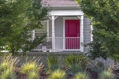 Porta da rua vermelha com ajardinar do jardim da frente Fotos de Stock