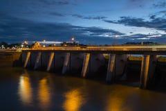 Porta de água da represa iluminada no crepúsculo Fotografia de Stock Royalty Free