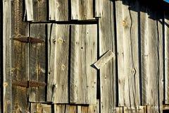 Porta de celeiro resistida velha com dobradiças oxidadas foto de stock