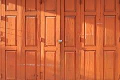 Porta de dobradura de madeira tailandesa retro alaranjada com o fechamento sob a luz solar da noite imagens de stock royalty free