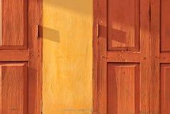 Porta de dobradura de madeira tailandesa retro alaranjada com a parede amarela sob a luz solar da noite imagens de stock