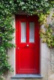 Porta de entrada vermelha com flores do jasmim Foto de Stock Royalty Free
