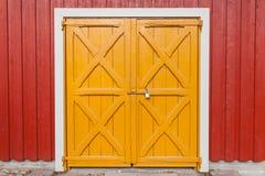 Porta de madeira amarela fechado na parede vermelha, fundo Fotos de Stock