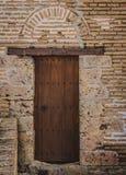 Porta de madeira antiga na parede de tijolo no palácio histórico espanhol Imagens de Stock