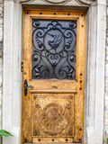 Porta de madeira bonita com teste padrão feito do ferro da cisne na casa velha na vila do Gruyère, cantão de Fribourg, Suíça, Eur Foto de Stock