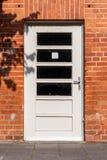 Porta de madeira branca com o vidro que enche-se na alvenaria foto de stock