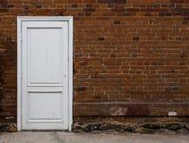 Porta de madeira branca em uma parede de tijolo velha. Foto de Stock Royalty Free