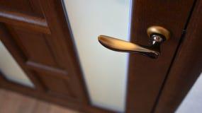 Porta de madeira de Brown com uma janela de vidro e um botão de porta de bronze fotografia de stock royalty free