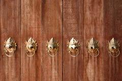 A porta de madeira com cabeça do garuda do ouro deu forma aos puxadores da porta Fotografia de Stock