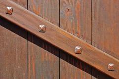 A porta de madeira com cinta prendeu com parafusos forjados Fotografia de Stock Royalty Free