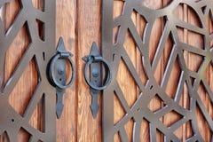 Porta de madeira com elementos forjados do metal fim redondo do punho do metal acima Textura do fundo fotografia de stock royalty free
