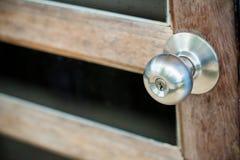 porta de madeira com grade, o botão de porta inoxidável ou o punho na porta de madeira na iluminação bonita fotografia de stock royalty free
