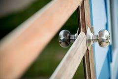 porta de madeira com grade, o botão de porta inoxidável ou o punho na porta de madeira na iluminação bonita fotos de stock