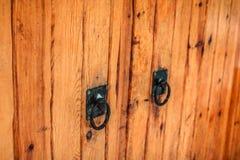 Porta de madeira com os punhos pretos do ferro Feche acima da vista foto de stock
