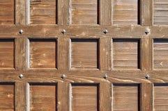 Porta de madeira com os rebites velhos do metal - fundo textured retro de Brown Foto de Stock
