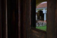 Porta de madeira com tom marrom escuro, espelhos em uma grande porta de madeira imagem de stock