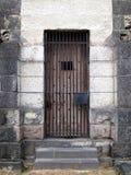 Porta de madeira da cadeia de pedra velha com barras de ferro Imagens de Stock Royalty Free