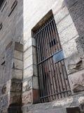 Porta de madeira da cadeia de pedra velha com barras de ferro imagem de stock royalty free