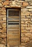 Porta de madeira envelhecida na parede de pedra da alvenaria Imagem de Stock Royalty Free