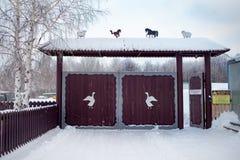 Porta de madeira no estilo tradicional do russo e neve ao redor no dia de inverno Figuras cinzeladas dos animais e dos pássaros d fotografia de stock royalty free