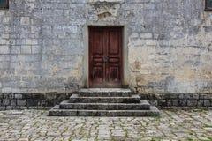 A porta de madeira obsoleta fechado e os tijolos de pedra pisam construção antiga Fotos de Stock Royalty Free