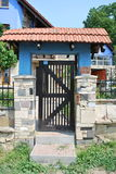 Porta de madeira preta, telha vermelha, pedra selvagem, coluna azul Imagem de Stock Royalty Free
