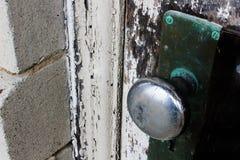A porta de madeira resistida com casca desvaneceu-se pintura na casa abandonada velha fotografia de stock