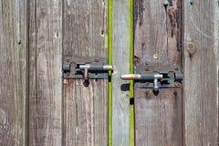 A porta de madeira velha com dois oxidou fechamentos metálicos fotografia de stock royalty free