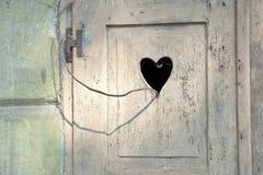 Porta de madeira velha com um coração romântico cinzelado Fotografia de Stock