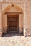 Porta de madeira velha em uma parede da lama Fotografia de Stock