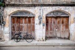A porta de madeira velha, o muro de cimento rústico e o vintage bike imagens de stock royalty free