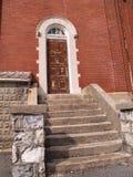 Porta de madeira velha por um edifício de tijolo vermelho Fotos de Stock