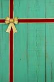 A porta de madeira velha verde antiga com vermelho e fita do Natal de veludo do ouro e o ouro curvam a beira Imagem de Stock