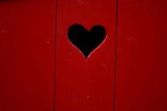 Porta de madeira vermelha com coração Fotos de Stock