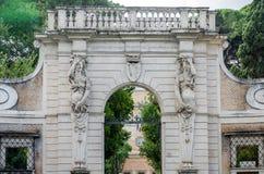 Porta de pedra para entrar no parque com colunas sob a forma de uma mulher humana com uma brasão e na crença na capital de Itália Imagem de Stock Royalty Free