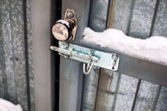 Porta del metallo con la manopola di porta e serrare neve coperta immagini stock