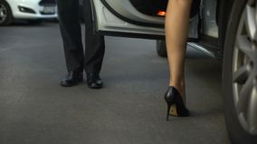 Porta del veicolo di apertura del signore, donna d'aiuto che entra nell'automobile, fine su delle gambe archivi video