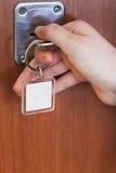 Porta della casa di apertura dalla chiave con keychain in bianco Fotografia Stock