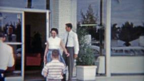 1959: Porta di apertura di saleman dell'automobile per signora ed il bambino Miami, Florida stock footage