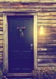 Porta di cabina rustica con la luce del portico Fotografia Stock Libera da Diritti