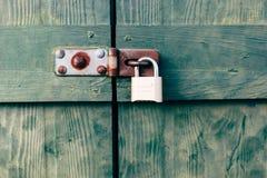 Porta di granaio verde di legno con una serratura di cuscinetto immagini stock