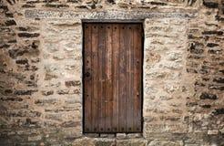 Porta di legno antica in parete di pietra del castello immagini stock libere da diritti