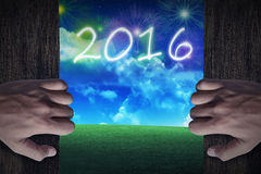 Porta di legno aperta della mano alla città che celebra il nuovo anno 2016 Fotografia Stock Libera da Diritti