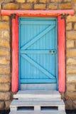 Porta di legno blu con la struttura rossa in vecchia parete di pietra fotografia stock