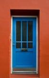 Porta di legno blu su una parete rossa Fotografie Stock Libere da Diritti