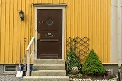 Porta di legno con il portico e l'inferriata, arborvitaes, abete rosso, giardino fotografie stock libere da diritti